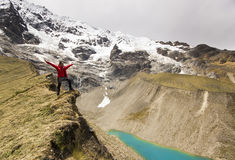 Man on the cliff in mountains at above lake stock photography