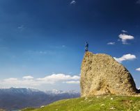 Man on the cliff in mountains at above sea Royalty Free Stock Image