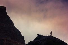 Man on a cliff in mountains Stock Photography
