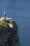 Man on cliff near lake Royalty Free Stock Photo