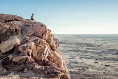Man on cliff over desert Stock Photos