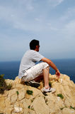 Man on cliff top. In spain with blue sky and sea background Stock Photo
