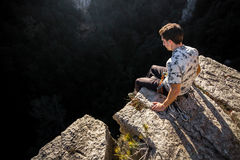 Man on a cliff. Young man with an age of 21 at the edge of a cliff after climbing the wall Royalty Free Stock Image