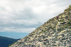 Man climb on mountain hill. A tourist makes its way through the stone placers Man climb on mountain hill stock image