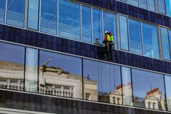 Man climb outside for cleaning window glass of high tower stock photo