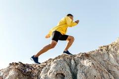 Man climb uphill mountain. In yellow jacket background sky stock photos