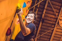 Man climber on artificial climbing wall in bouldering gym Royalty Free Stock Photography