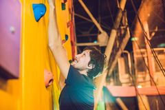 Man climber on artificial climbing wall in bouldering gym Stock Image