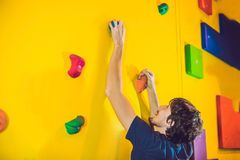 Man climber on artificial climbing wall in bouldering gym Stock Photo