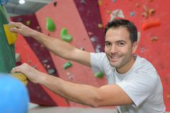 Man climber on artificial climbing wall in bouldering gym Royalty Free Stock Photos
