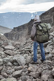 Man climber with a backpack looking at the stony pass in mountains, rear view Royalty Free Stock Photo