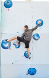 Man climber climbs a bouldering problem on climbing gym Royalty Free Stock Image