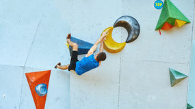 Man climber climbs a bouldering problem on climbing gym Royalty Free Stock Photos