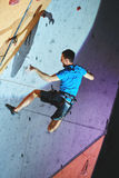 Man climber climbs a with rope on climbing gym and falling. Man climber climbs with rope on climbing gym. man mekes hard wide move and falling. Climbing Royalty Free Stock Image