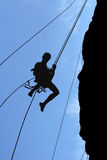 Man-climber rises on the wall. A man-climber rises on the wall with the help of the ropes Stock Image