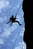 Man-climber & ropes. A man-climber rises on the wall with the help of the ropes Royalty Free Stock Image
