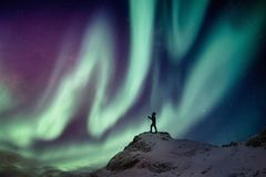 Man climber standing on snowy peak with aurora borealis and starry royalty free stock images