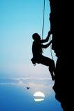 Man climber at sunset Stock Photos