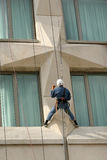 Man climbing. Man working, climbing a building Stock Image