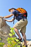 Man climbing. Middle aged man with backpack climbing a rock Stock Image