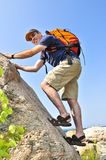 Man climbing. Middle aged man with backpack climbing a rock royalty free stock images