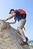 Man climbing. Middle aged man with backpack climbing a rock stock photo