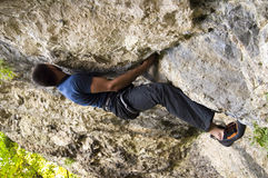 Man climbing a boulder. A rock climber climbing a cliff in the woods Royalty Free Stock Photography