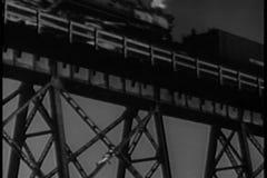 Man climbing bridge as train passes overhead stock video