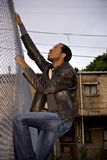 Man climbing city fence. A view of a young 22-year old African-American man climbing a chain link fence in a city setting Royalty Free Stock Photos