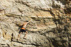 Man climbing a cliff. Young man climbing a cliff above sea Royalty Free Stock Photos