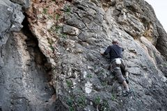 Man climbing cliff Royalty Free Stock Images