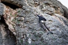 Man climbing cliff Stock Photo