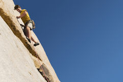 Man Climbing On Cliff. Low angle view of a man climbing on cliff against clear blue sky Royalty Free Stock Image