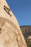 Man Climbing On Cliff. Low angle view of a man climbing on cliff against clear blue sky Royalty Free Stock Photography