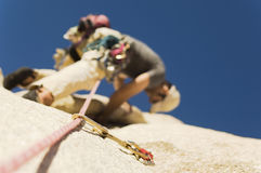 Man Climbing On Cliff. Low angle view of a man climbing on cliff against sky Royalty Free Stock Photos