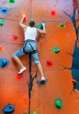Man climbing on a climbing wall. Training in insurance stock image