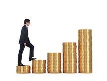 Man climbing on coins Royalty Free Stock Photos