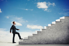 Man climbing concrete stairs in a light cloudy sky stock photos
