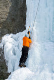 Man climbing frozen waterfall Royalty Free Stock Photography