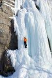 Man climbing frozen waterfall Stock Images