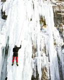 Man climbing frozen waterfall. royalty free stock images