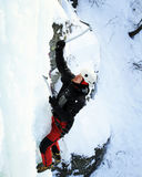Man climbing frozen waterfall. stock photo