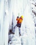 Man climbing frozen waterfall. Stock Image