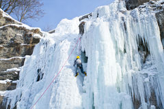 Man climbing frozen waterfall Stock Photo