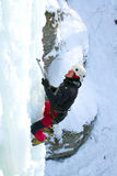 Man climbing frozen waterfall Stock Images