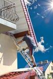 Man climbing the high position. Of the haus stock photos
