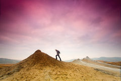 Man climbing a hill with colorful clouds. Stock Photos