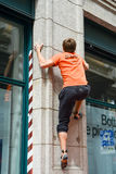 Man climbing a house wall on street boulder contest Stock Photos