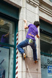 Man climbing a house wall on street boulder contest Royalty Free Stock Images