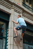 Man climbing a house wall on street boulder contest Royalty Free Stock Photography
